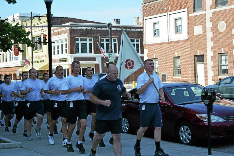 The new firefighters on a run Tuesday morning as part of their training, running with them is firefighter Jay Dixon and Training Officer David Tripp. Photo: Jenny Golfin — Register Citizen