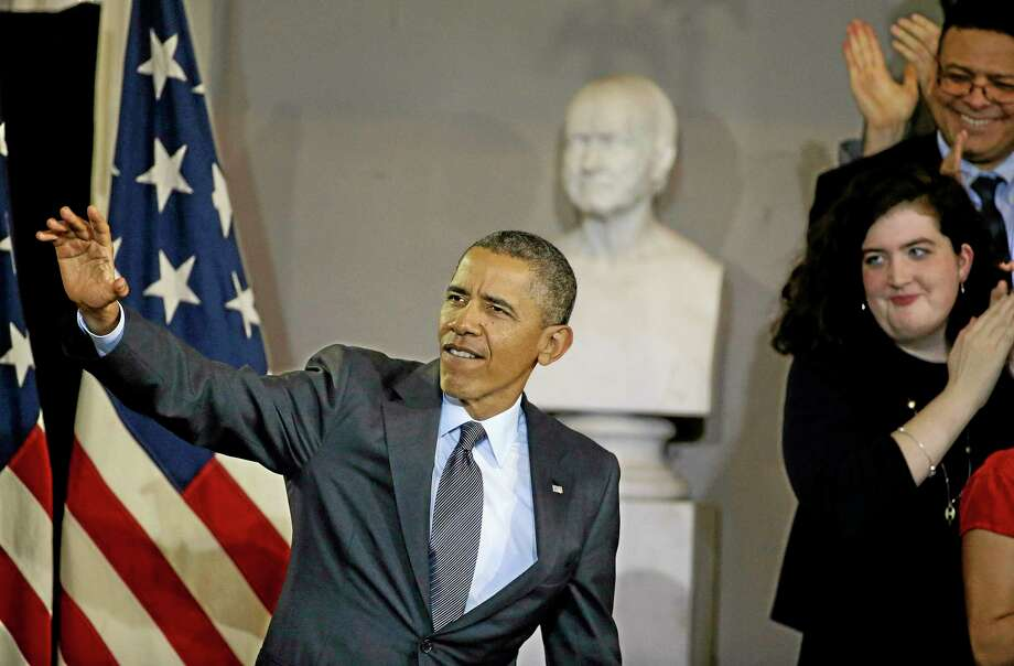 President Barack Obama waves before he speaks at Boston's historic Faneuil Hall about the federal health care law, Wednesday, Oct. 30, 2013. Faneuil Hall is where former Massachusetts Republican Gov. Mitt Romney, Obama's rival in the 2012 presidential election, signed the state's landmark health care law in 2006(AP Photo/Stephan Savoia) Photo: AP / AP