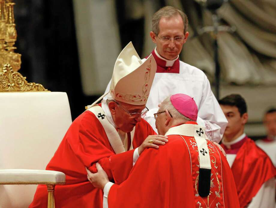 Pope Francis greets Leonard Paul Blair, kneeling, archbishop of Hartford, after bestowing on him the pallium, a woolen shawl symbolizing a bishop's bond with the pope, during Sunday Mass in St. Peter's Basilica at the Vatican. Photo: AP Photo — Riccardo De Luca   / AP