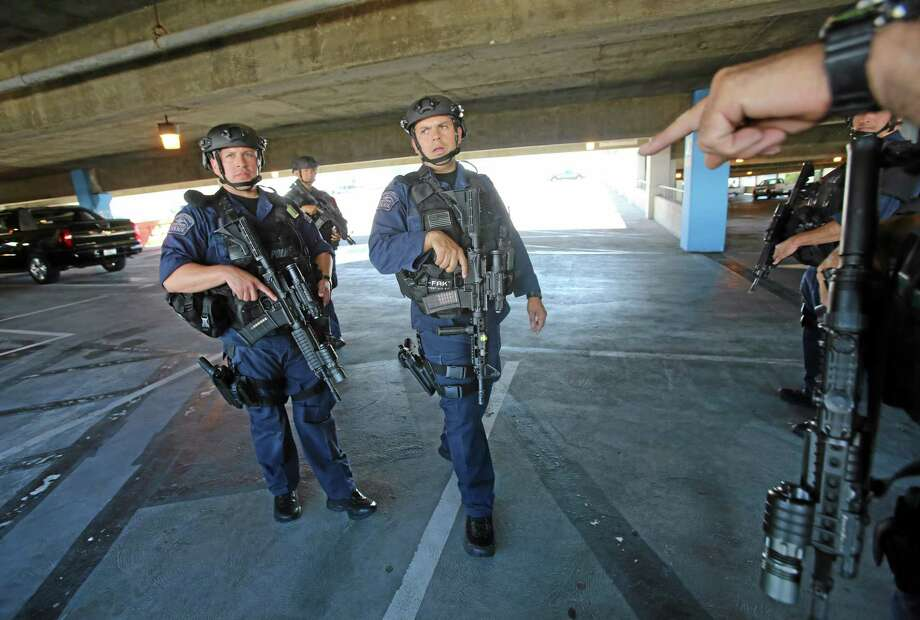 SWAT officers search a parking structure during a security check at Los Angeles International Airport on Friday Nov. 1, 2013. A gunman armed with a semi-automatic rifle opened fire at the airport on Friday, killing a Transportation Security Administration employee and wounding two other people. Photo: Ringo H.W. Chiu—The Associated Press  / FR170512 AP