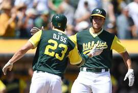 OAKLAND, CA - AUGUST 27:  Matt Olson #28 and Matt Joyce #23 of the Oakland Athletics celebrates after Olson hit a two-run homer against the Texas Rangers in the bottom of the second inning at Oakland Alameda Coliseum on August 27, 2017 in Oakland, California.  (Photo by Thearon W. Henderson/Getty Images)