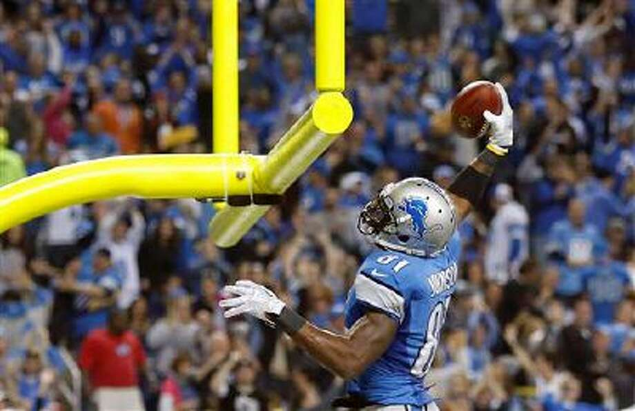 Detroit Lions wide receiver Calvin Johnson (81) prepares to dunk the football after his 20-yard touchdown run during the third quarter of an NFL football game against the Green Bay Packers at Ford Field in Detroit, Thursday, Nov. 28, 2013. (AP Photo/Rick Osentoski) Photo: AP / FR170444 AP