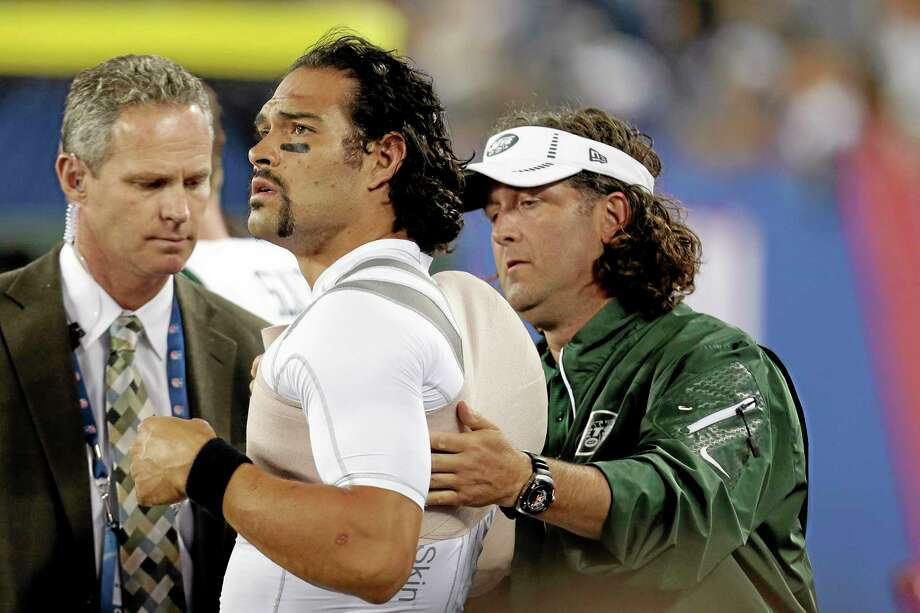 A trainer wraps New York Jets quarterback Mark Sanchez, center, during the second half of a preseason game against the Giants on Saturday. Photo: Julio Cortez — The Associated Press  / AP