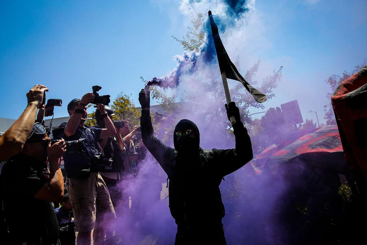 An anarchist holds a smoke bomb after the police retreat during a protest at Martin Luther King Jr. Civic Center park in Berkeley, Calif., on Sunday, August 27th, 2017.