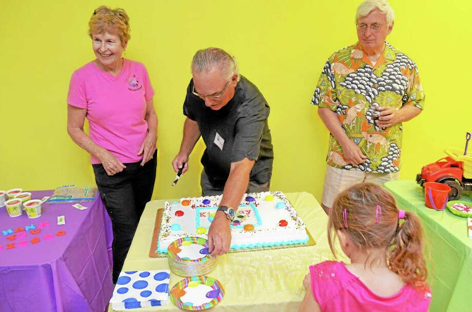 A cake celebrating one year of KidsPlay was cut at their anniversary party Saturday night. Left to right, Cathy Schmitz, Stuart Grodin, and Ken Merz serve up the cake. Photo: John Berry - Register Citizen
