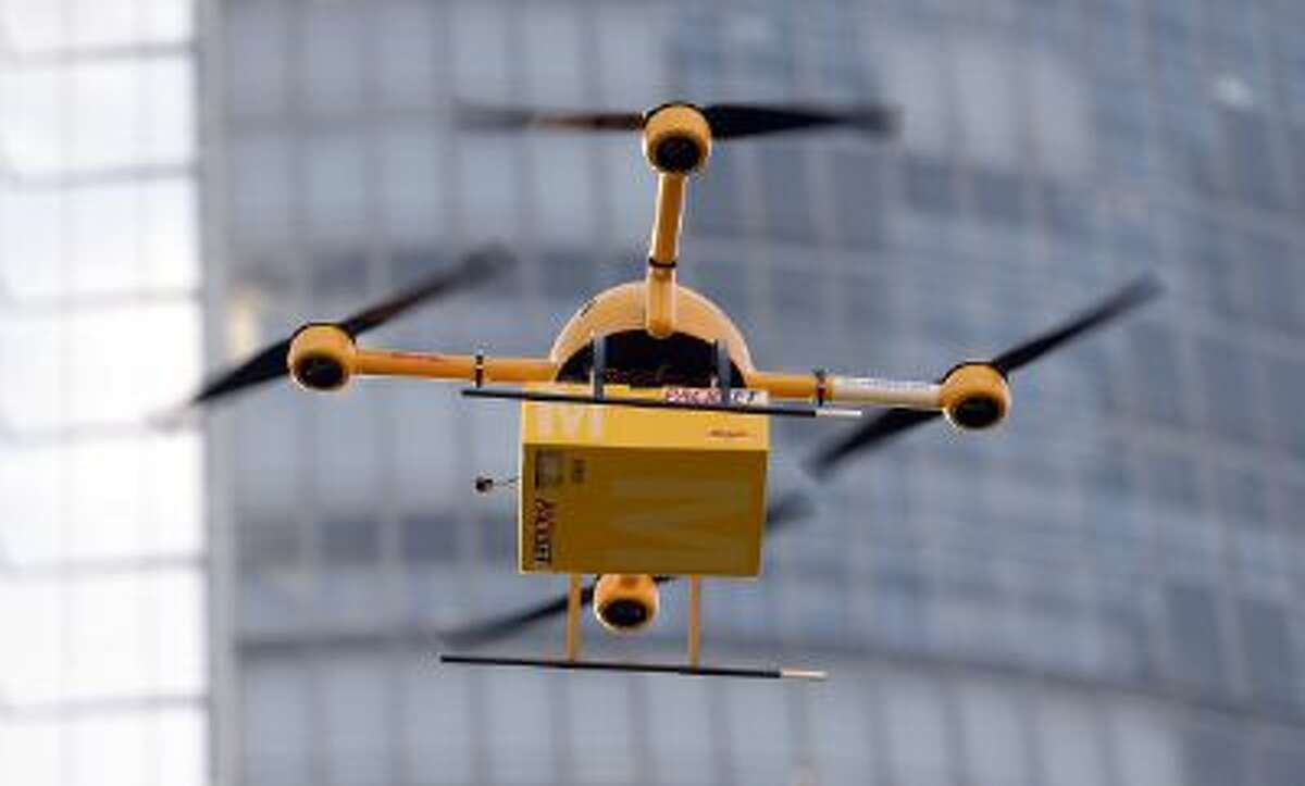 A quadrocopter drone controlled remotely transports a post package during a test flight for the Deutsche Post DHL in Bonn, western Germany. The Deutsche Post tests a system for delivering urgent packages via drone over short distances.