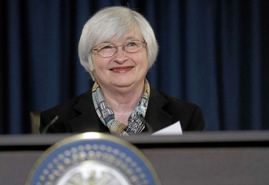 Federal Reserve Chair Janet Yellen smiles during her first news conference at the Federal Reserve in Washington, Wednesday, March 19, 2014. The Federal Reserve is seeking to clarify when it might start to raise short-term interest rates from record lows. The Fed also says it will cut its monthly long-term bond purchases by another $10 billion to $55 billion because it thinks the economy is strong enough to support further improvements in the job market.  (AP Photo/Susan Walsh) Photo: AP / AP