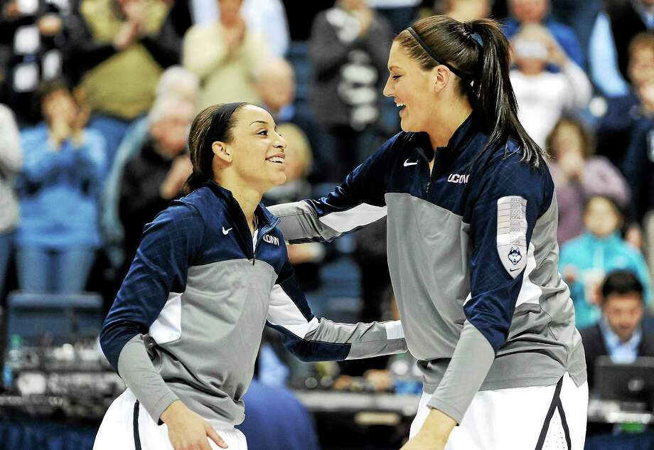 Associated Press Connecticut seniors Bria Hartley, left, and Stefanie Dolson, right, embrace after they are are honored at senior night before a game against Rutgers March 1. Dolson and Hartley say they are more focused on winning tonight than playing their final game at Gampel. Photo: AP / AP2014