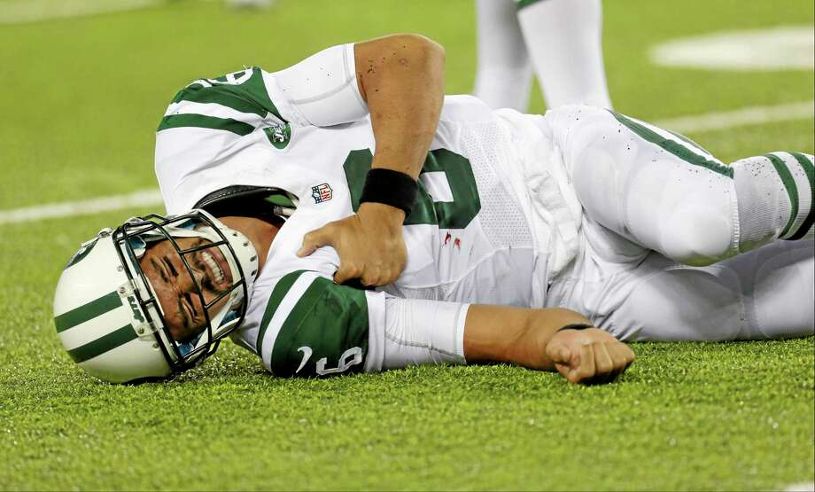 New York Jets quarterback Mark Sanchez reacts to an injury during the second half against the New York Giants Saturday. He left the game with what appeared to be a shoulder injury. Photo: Julio Cortez — The Associated Press  / AP