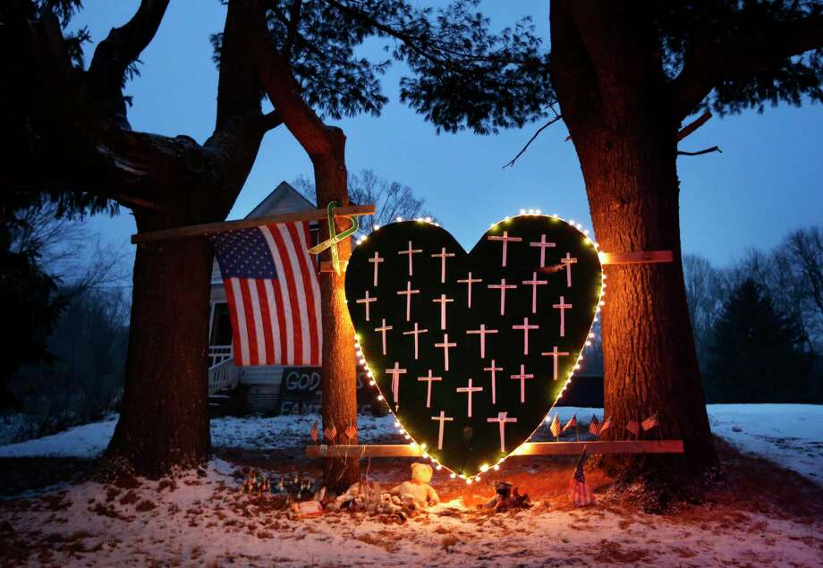 FILE - In this Dec. 14, 2013 file photo, a makeshift memorial with crosses for the victims of the Sandy Hook Elementary School shooting massacre stands outside a home in Newtown, Conn., on the one-year anniversary of the shootings. Newtown is taking its time to decide what a permanent memorial should look like. A commission has been hearing proposals for concepts including murals, groves and memorial parks, while looking for lessons from paths chosen by other tragedy-stricken communities. Public forums are planned for 2015, the next step in a process that is expected to last several more years. (AP Photo/Robert F. Bukaty, File) Photo: AP / AP