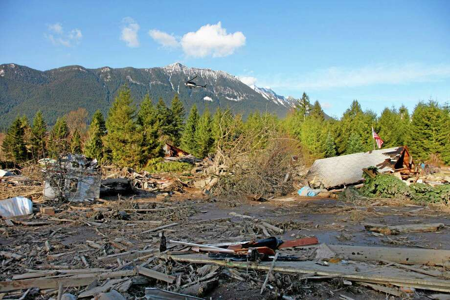 A search helicopter flies above the area Sunday where a fatal mudslide washed over the land Saturday morning near Oso, Wash., Sunday, March 23, 2014. A flag sits atop what was Cory Kuntz and family's home Sunday afternoon. The family was at a baseball game Saturday morning when the fatal mudslide swept through the area, destroying everything on their property. (AP Photo /The Herald, Genna Martin) Photo: AP / The Herald