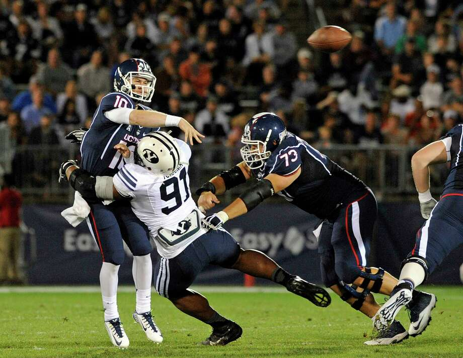 UConn quarterback Chandler Whitmer gets pressured by BYU defensive lineman Travis Tuiloma (91) during the first half of the Huskies' 35-10 loss on Friday night at Rentschler Field in East Hartford. Photo: Fred Beckham — The Associated Press  / FR153656 AP