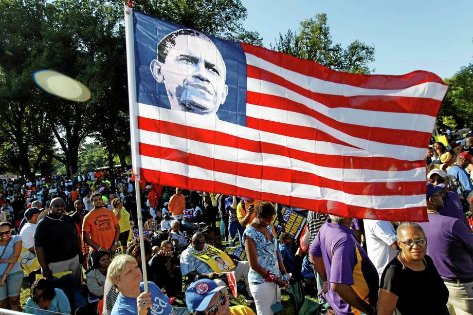 Dorothy Meekins holds up the  national flag with the picture of President Barack Obama as she attends the rally, commemorating the 50th anniversary of the 1963 March on Washington at the Lincoln Memorial in Washington, Saturday, Aug. 24, 2013. Organizers have planned for about 100,000 people to participate in the event, which is the precursor to the actual anniversary of the Aug. 28, 1963, march. It will be led by the Rev. Al Sharpton and King's son Martin Luther King III. (AP Photo/Jose Luis Magana) Photo: AP / FR159526 AP