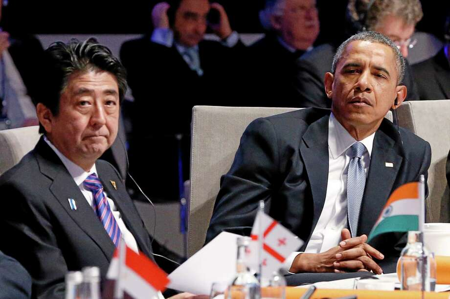 Japan's Prime Minister Shinzo Abe, left, and U.S. President Barack Obama, right, attend the opening session of the Nuclear Summit in The Hague, Netherlands, on Monday, March 24, 2014. Obama gathered with world leaders in a day of delicate diplomacy, as he sought to rally the international community Monday around efforts to isolate Russia following its incursion into Ukraine. Nuclear terrorism was the official topic as Obama and other world leaders streamed in to a convention center in The Hague for a two-day nuclear summit. But the real focus was on a hurriedly scheduled meeting of the Group of Seven industrialized economies to address the crisis in Ukraine on the sidelines of the nuclear summit. (AP Photo/Yves Herman, Pool) Photo: AP / AP 2014