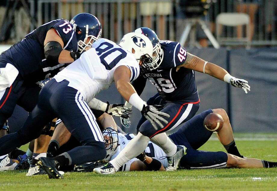 UConn tight end Sean McQuillan (49) and BYU's Bronson Kaufusi (90) fight for a loose ball after a Connecticut fumble during the first half of the Huskies' 35-10 loss on Friday night at Rentschler Field in East Hartford. Photo: Fred Beckham — The Associated Press  / FR153656 AP