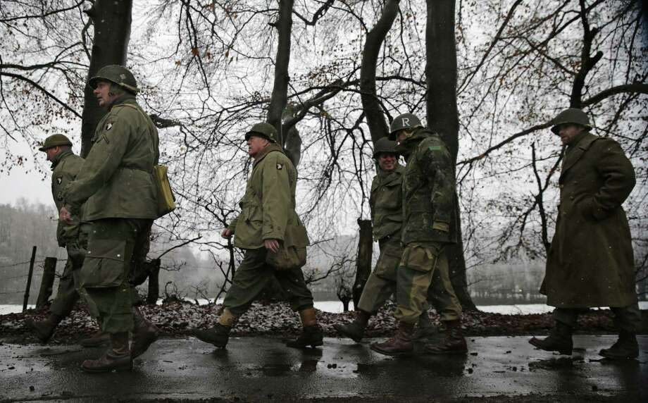 Re-enactors dressed as US WWII soldiers walk along a road during the 70th anniversary of the Battle of the Bulge or the Ardennes Offensive, in Bastogne, southeastern Belgium, Saturday, Dec. 13, 2014. The Battle of the Bulge was fought in dense forests and narrow valleys of the Belgian and Luxembourg Ardennes and was one of the bloodiest battles of World War II. (AP Photo/Yves Logghe) Photo: AP / AP