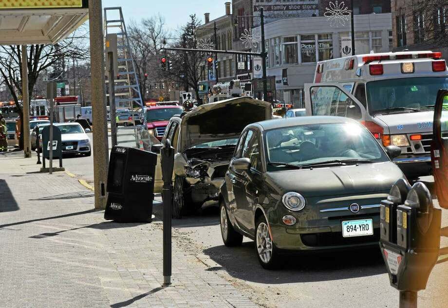 A Subaru Forester, center, sustained damage after striking two parked cars on Main Street in Torrington Monday afternoon. The driver suffered minor injuries and was transported to the hospital. Photo: Jenny Golfin — Register Citizen