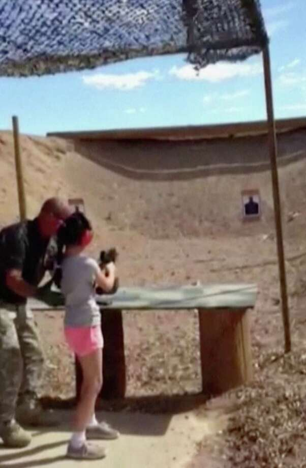 In this Aug. 25, 2014 image made from video provided by the Mohave County Sheriff Department, firing-range instructor Charles Vacca, left, shows a 9-year old girl how to use an Uzi. Vacca, 39, was standing next to the girl on Monday at the Last Stop range in Arizona, south of Las Vegas, when the girl squeezed the trigger, causing the Uzi to recoil upward and shoot Vacca in the head. Photo: AP Photo/Mohave County Sheriff Department  / Mohave County Sheriff Department