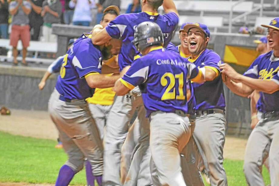The Tri-Town Trojans mob Landon Gardella at home plate after he scored the game-winning and series-winning run in the bottom of the 12th on a throwing error by Naugatuck's shortstop Macky Cianciolo. Photo: Pete Paguaga—Register Citizen