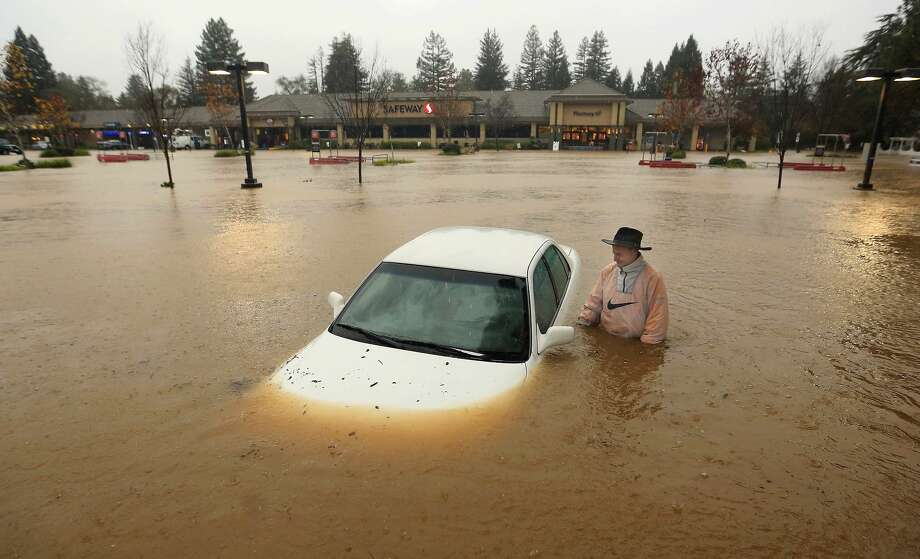 A resident of Guerneville, Calif., who parked his car overnight in the Safeway parking lot on Vine Street in Healdsburg, Calif.,  finds it nearly completely submerged as Foss Creek topped it's banks, Thursday morning, Dec. 11, 2014. A powerful storm churned down the West Coast Thursday, bringing strong gales and much-needed rain and snow that caused widespread blackouts in Northern California and whiteouts in the Sierra Nevada. Sonoma County authorities are recommending hundreds of people evacuate the lowest lying areas near the Russian River, which is projected to start overflowing overnight.  (AP Photo, The Press Democrat, Kent Porter) Photo: AP / The Press Democrat