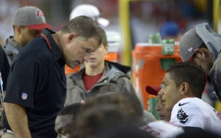In this Sept. 15, 2013 file photo, Tampa Bay Buccaneers head coach Greg Schiano, left, talks to quarterback Josh Freeman (5) during the second quarter of an NFL football game against the Tampa Bay Buccaneers, in Tampa, Fla.