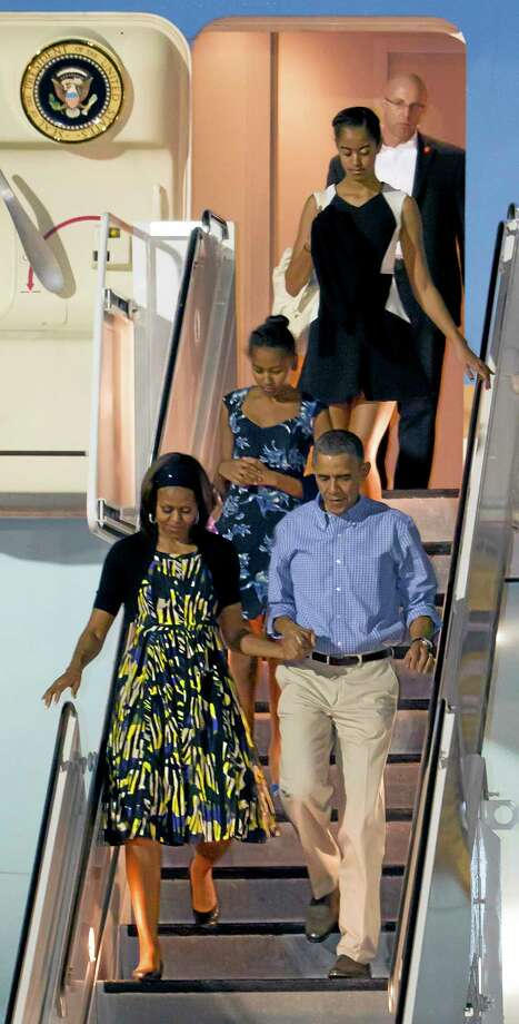 President Barack Obama, bottom right, and first lady Michelle Obama, bottom left, along with their daughters  Sasha, middle, and Malia, top, disembark Air Force One after arriving at Joint Base Pearl Harbor-Hickam for their family Christmas vacation, Friday, Dec. 20, 2013, in Honolulu. The first family will be spending their vacation in Hawaii and return to Washington on Jan. 5, 2014. (AP Photo/Eugene Tanner) Photo: AP / FR168001 AP