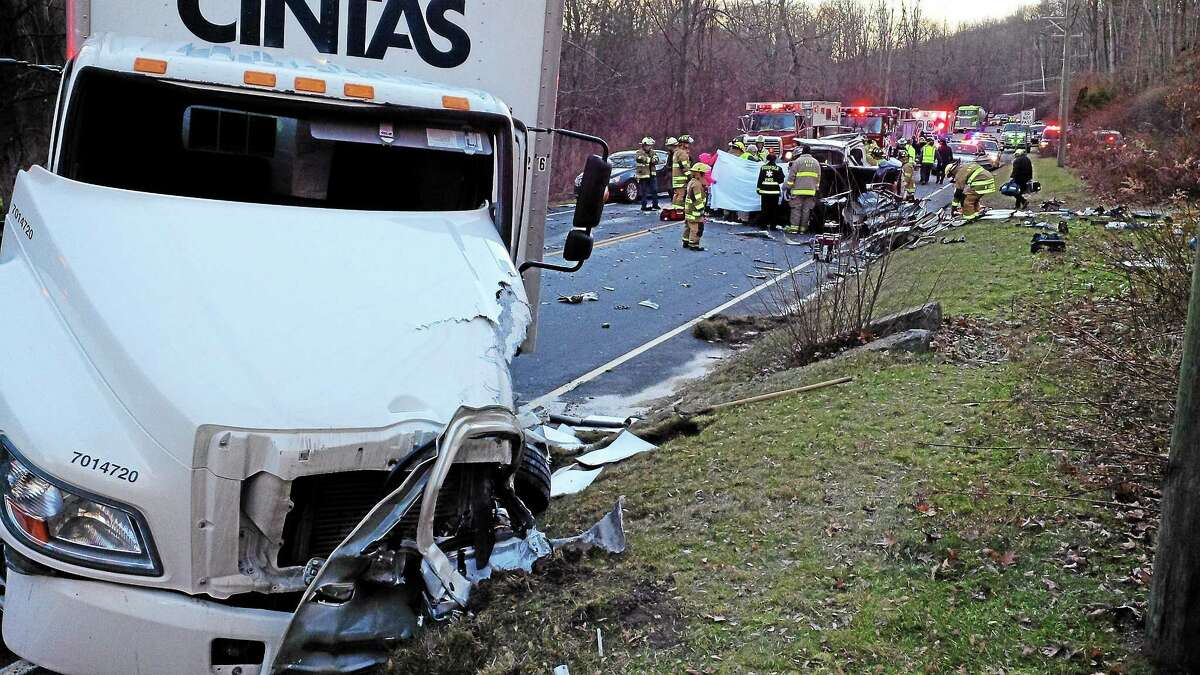 Firefighters at the scene of a fatal accident on Route 44 in Norfolk involving a box truck and sports-utility vehicle. The SUV's driver was killed.