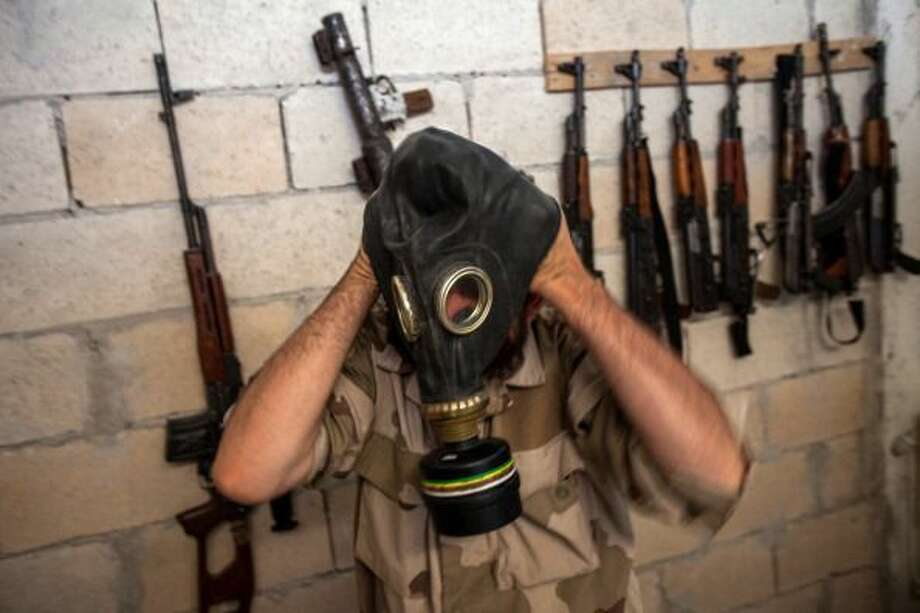 A Syrian rebel tries on a gas mask seized from a Syrian army factory in the northwestern province of Idlib on July 18. (Daniel Leal-Olivas/AFP/Getty Images)