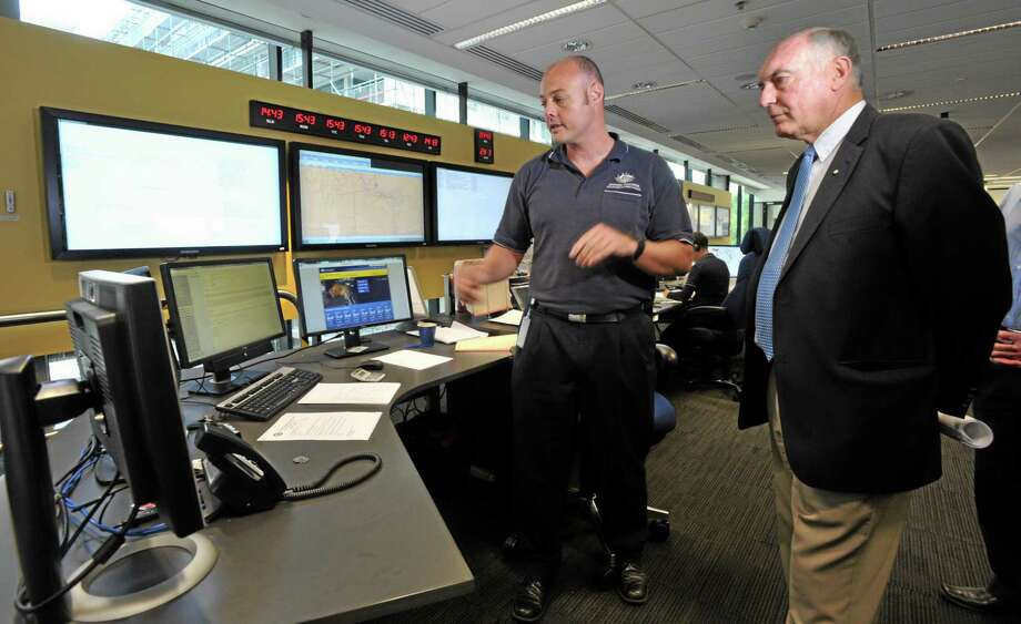 Australia's Deputy Prime Minister Warren Truss, right, and Dan Gillis, senior search and rescue officer involved in the search for the missing Malaysia Airlines Flight MH370, watch monitor at the Australian Maritime Safety Authority's rescue coordination center in Canberra, Sunday, March 23. 2014. Planes and ships scrambled Sunday to find a pallet and other debris in a remote patch of the southern Indian Ocean to determine whether the objects were from the Malaysia Airlines jet that has been missing for more than two weeks. AP Photo/Graham Tidy, Pool Photo: AP / Canberra Times Pool