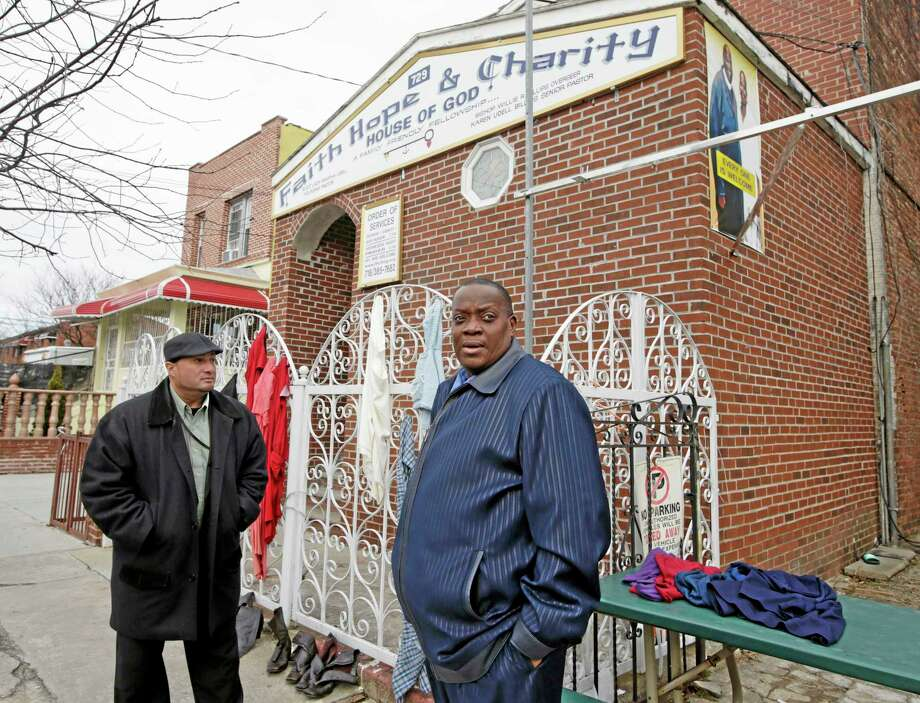 Bishop Willie Billips, right, and his assistant Brother Jose Vella stand outside Faith, Hope and Charity Church of God in the Brownsville section of Brooklyn, Monday, Dec. 30, 2013, in New York, after hanging donated clothing on the fence. Billips, 51, a Brownsville native who specializes in working with gang members, credits New York Police Chief Ray Kelly and police commanders and police commanders with teaming up with the clergy and community activists in the neighborhood to try to curb crime. But year-end boasts by Mayor Michael Bloomberg that New York is the safest big city in America ring hollow in Brownsville, a neighborhood of entrenched gang violence that has proven stubbornly immune to strategies that have pushed crime to historic lows across the rest of the city. (AP Photo/Kathy Willens) Photo: AP / AP