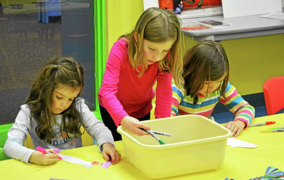 From left to right, Emma Davis, Emily Cole and Isabella Davis take part in an art project at KidsPlay in Torringotn Sunday.  Ryan Flynn - The Register Citizen Photo: Journal Register Co.