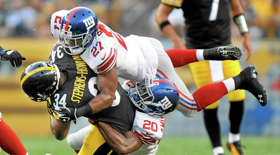 Pittsburgh Steelers running back LaRod Stephens-Howling (34) is tackled by New York Giants strong safety Stevie Brown (27) and cornerback Prince Amukamara (20) on a run during the first quarter of an NFL preseason football game Saturday, Aug. 10, 2013, in Pittsburgh. (AP Photo/Don Wright) Photo: AP / FR87040 AP