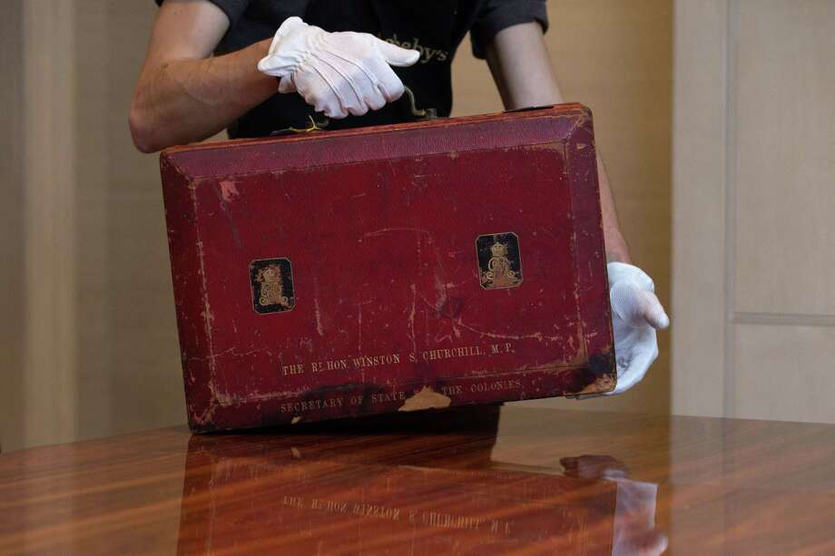 In this photo taken Dec. 9, 2014, a member of Sotheby's staff poses for a picture with Churchillís red morocco leather dispatch box from his time as Secretary of State for The Colonies: the lid stamped 'THE RT HON WINSTON CHURCHILL. MP SECRETARY OF STATE FOR THE COLONIES' at the auction house in London, England. Photo: AP Photo/Tim Ireland  / AP