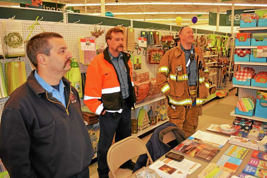 Deputy Fire Marshal Jarred Howe (left) and other fire personnel greeting customers inside JoAnn Fabrics. Photo: Ryan Flynn - The Register Citizen