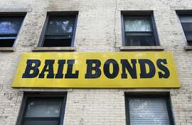 In this photo taken Tuesday, July 7, 2015, a bail bonds sign hangs on the side of a bail bonds business near Brooklyn's courthouse complex and jail in New York. Officials say they�re eliminating cash bail for thousands of New Yorkers accused of misdemeanor and non-violent felonies in an effort to divert them from the Rikers Island jail complex. An $18 million plan to be unveiled Wednesday, July 8, will allow judges to instead require that people accused of certain crimes be monitored while they wait for their trial. (AP Photo/Kathy Willens)