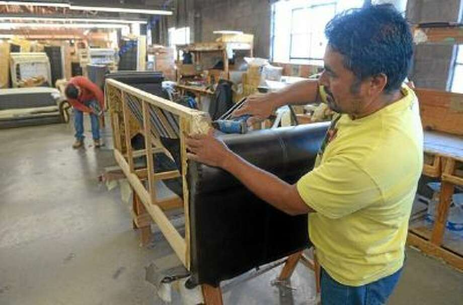 Victor Hernandez staples vinyl fabric onto a couch he's assembling at Cambridge of California in Gardena, CA on Tuesday, December 10, 2013.