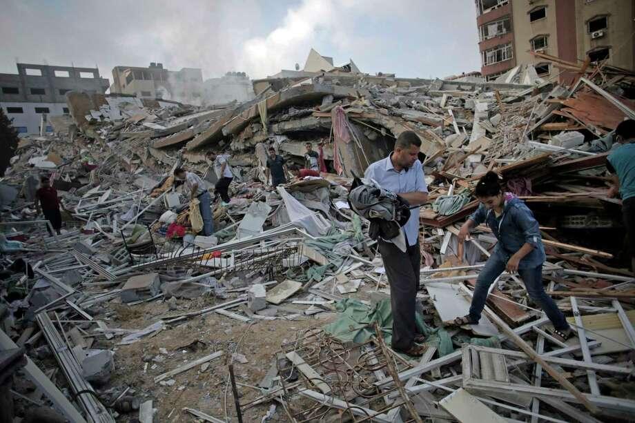 Smoke, dust and debris rise after an Israeli strike hit Gaza City in the northern Gaza Strip, Wednesday, Aug. 20, 2014. (AP Photo/Adel Hana) Photo: AP / AP