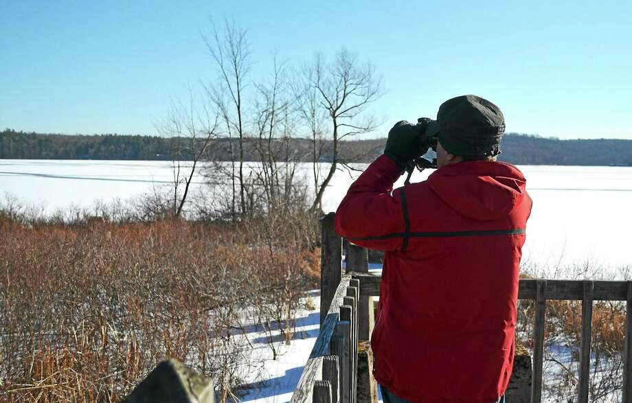 Steve Karsh looks out over the snow-covered Bantam Lake during an organized group hike at White Memorial Conservation Center in Litchfield. Photo: John Berry - The Register Citizen