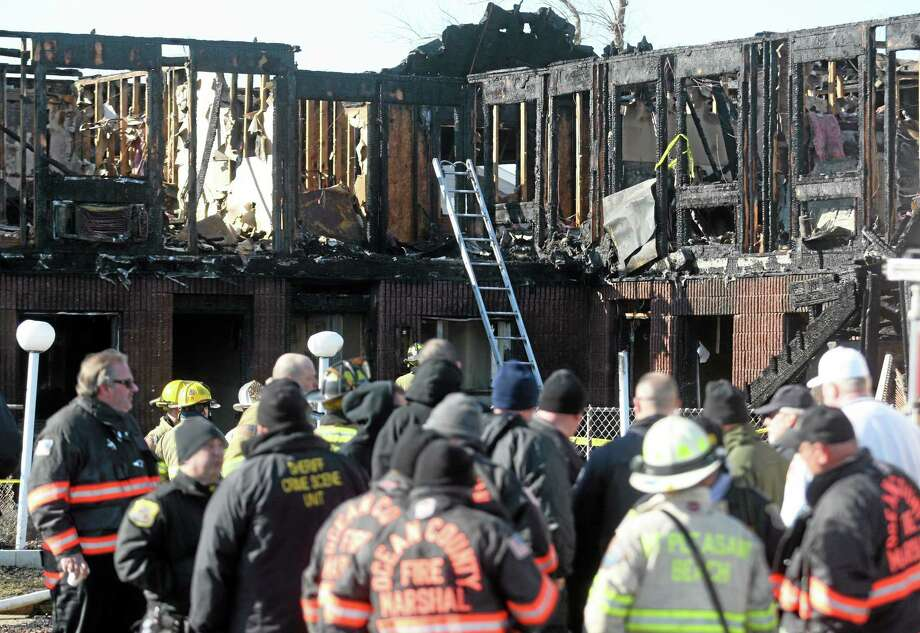 Firefighters investigate an early morning fire at the Mariner's Cove Hotel in Point Pleasant Beach, N.J. on Friday, March 21, 2014.  An early morning fire killed three people at the Jersey shore motel whose residents included Superstorm Sandy victims who were staying there because their homes remain uninhabitable nearly a year and a half after the storm, officials said. Three other people were critically injured in the blaze.  Authorities said several other people may be unaccounted for. Investigators are interviewing motel management to determine how many people were staying there when the fire broke out. The motel's office was destroyed and most records were lost.  (AP Photo/David Gard) Photo: AP / FR158623 AP
