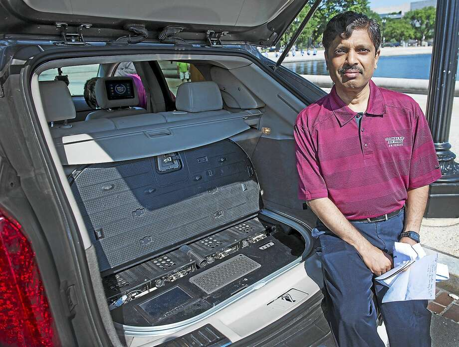 Carnegie Mellon University Professor Raj Rajkumar is shown with the main, multi-computer control center in the rear cargo area of a self-driven car that was on display in Washington on June 24. The car has been retrofitted with cameras and sensors to detect traffic lights, pedestrians and read some road signs. Photo: Washington Post Photo By Linda Davidson  / THE WASHINGTON POST