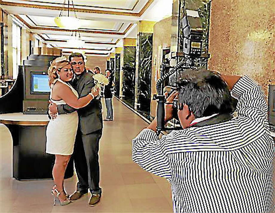 Wedding photographer Braulio Cuenca poses groom Jorge Mejia and bride Irma Aguilar, of the Bronx borough of New York, inside before their ceremony in New York's Office of the City Clerk, Wednesday Aug. 7, 2013. Photo: Richard Drew—The Associated Press  / AP