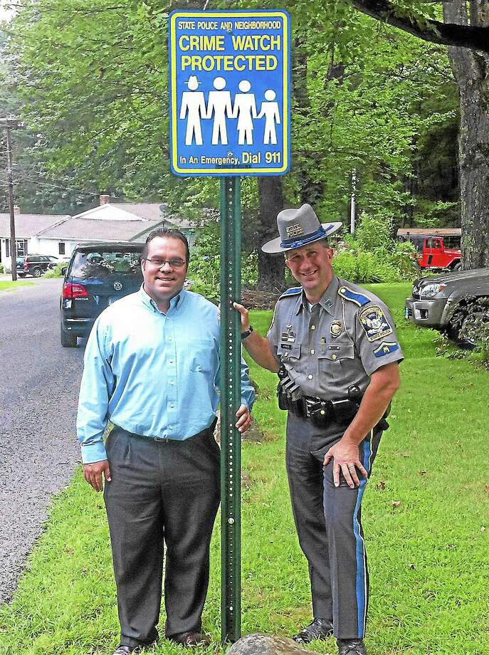 Harwinton First Selectman Michael Criss and resident State Trooper Bill Arbour with one of the town's new neighborhood watch signs. Photo: Contributed Photo
