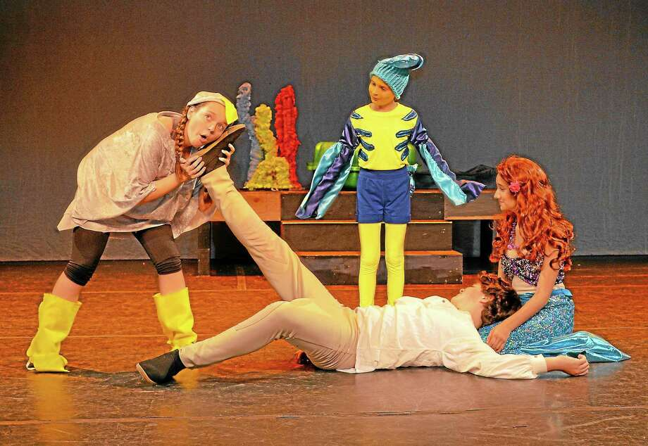Submitted photo - Alison GothScuttle the seagull (left) demonstrates his questionable expertise of human beings by taking a shipwrecked Prince Eric's pulse - through his foot - while Ariel (right) and Flounder look on. Scuttle is played by Middlebury resident Lauren Stango; Ariel by Thomaston resident Veronica Johnson; Flounder by Morris resident Kennedy Morris; and Prince Eric by Naugatuck resident Michael Newman. Photo: Journal Register Co.