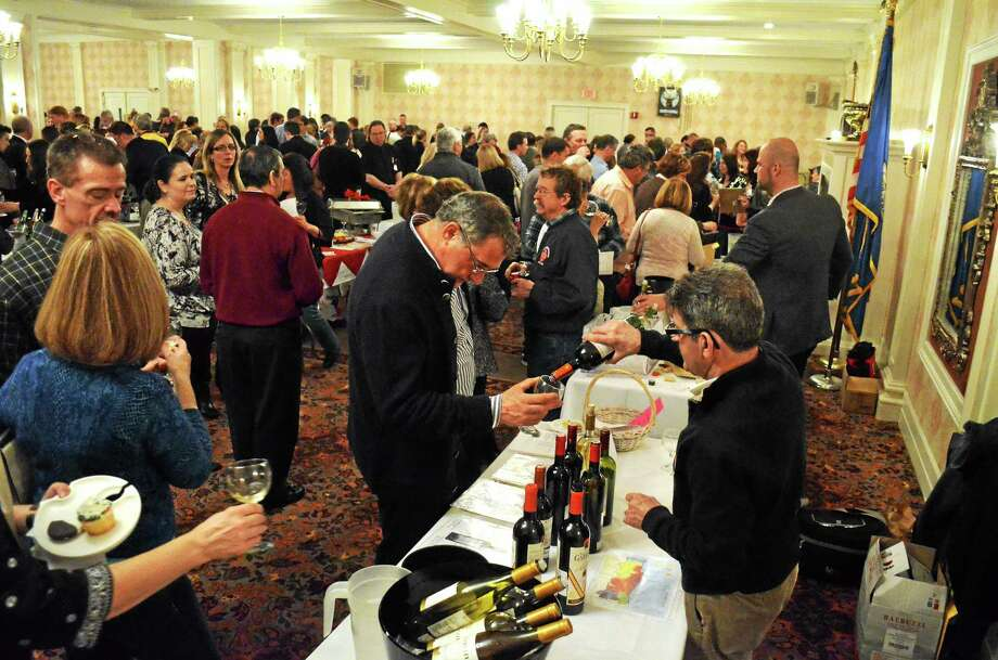 The grand ballroom was packed at the Elks Club in Torrington as LARC's annual wine tasting fundraiser brought wine lovers to sample a wide variety of beverages from distributors and wineries around the region. In the foreground, Fernando Ferreira of Iberia Wine and Spirits pours a sample.  John Berry - The Register Citizen Photo: Journal Register Co.