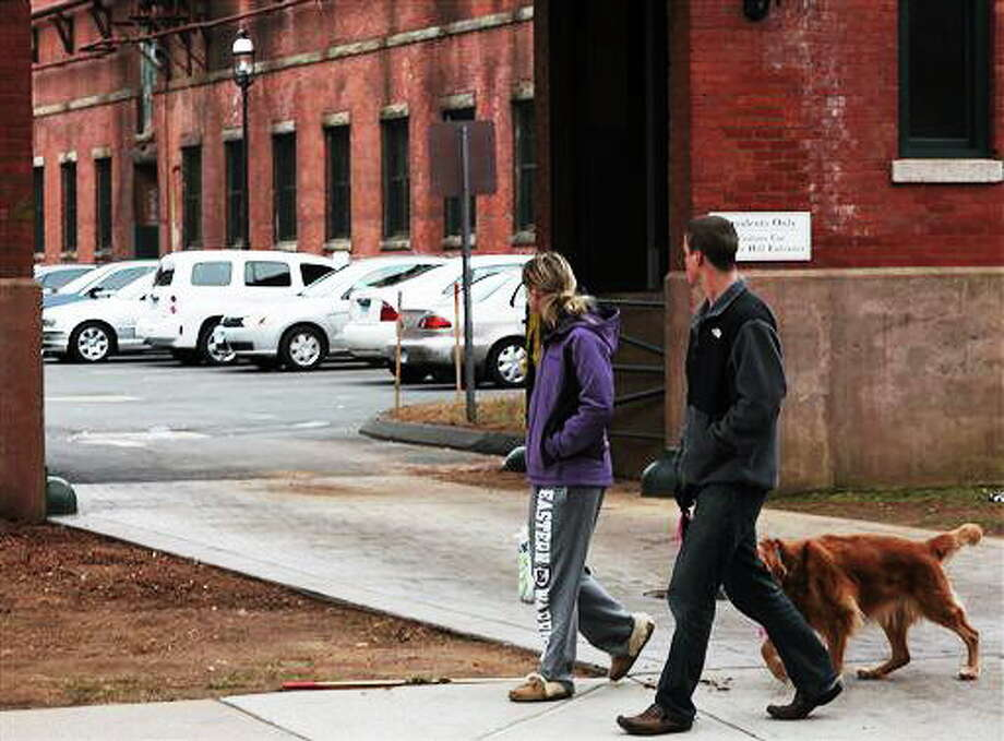 Neighbors walk by the scene where a triple murder-suicide occurred on Sunday, Dec. 8, 2013 in Manchester, Conn.  A triple murder-suicide that occurred late Saturday evening at the Dye House Apartments is being investigated by the Manchester Police Department and the Connecticut State Police. Officers received reports of shots fired near 190 Pine Street at 9:40pm on . Police quickly responded and confronted a man in a parking lot carrying a 13 month old child. The man then placed the child on the ground and shot himself. Three women were discovered in one unit in the building dead from apparent gunshot wounds. (AP Photo/Journal Inquirer, Jared Ramsdell) Photo: AP / Journal Inquirer