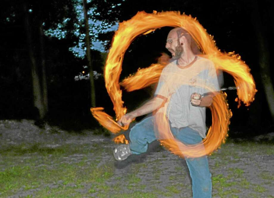 Eugene Sterling is one of the Torrington Area Fire Performers who perform at the Main Street Marketplace, seen here during a practice session Wednesday. Photo: John Berry—Register Citizen