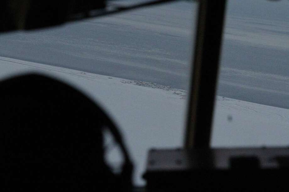 This photo taken Dec. 6, 2014, shows the community of Shishmaref, Alaska, as seen from the cockpit of an approaching  C130 military transport plane. The Alaska National Guard provided transport for the good Samaritan program Operation Santa, which took gifts and schools supplies to about 300 children in the Inupiat Eskimo community. (AP Photo/Mark Thiessen) Photo: AP / AP