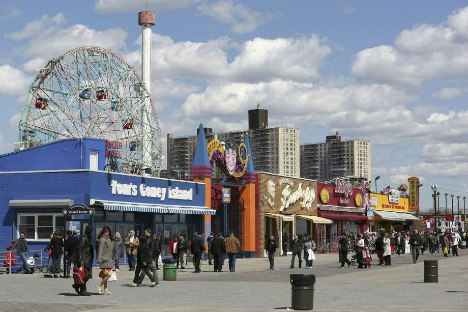 In a 2013 photo, visitors to New York's Coney Island walk on the boardwalk past the open businesses. Photo: AP File Photo  / AP