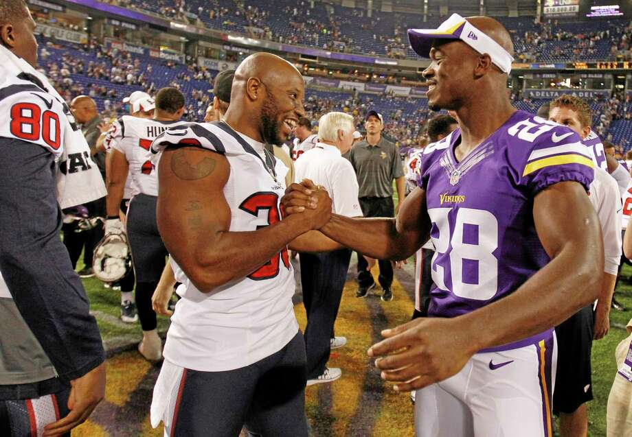 Minnesota Vikings running back Adrian Peterson (28) chats with Houston Texans free safety Danieal Manning (38) after an NFL preseason football game, Friday, Aug. 9, 2013, in Minneapolis. The Texans won 27-13. (AP Photo/Genevieve Ross) Photo: AP / FR170496 AP