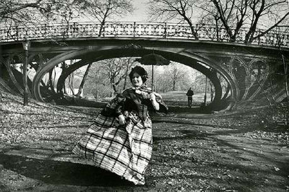 """This photo provided by the New-York Historical Society shows the photographer Bill Cunningham's muse Editta Sherman in front of the Gothic bridge in Central Park, which was designed in 1860, in New York. The photo is one of 88 prints from Bill Cunningham's 1976-1978 project, """"Facades,"""" featured in an exhibition at the New-York Historical Society, running through June 15, 2014. The images are a whimsical photo essay in which Cunningham posed models in period costumes against famous New York City historic sites of the same vintage. (AP Photo/New-York Historical Society, Gift of Bill Cunningham) Photo: AP / New-York Historical Society"""